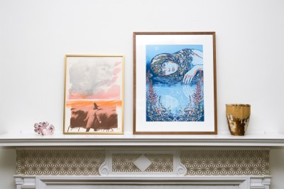 Two framed posters on a mantle